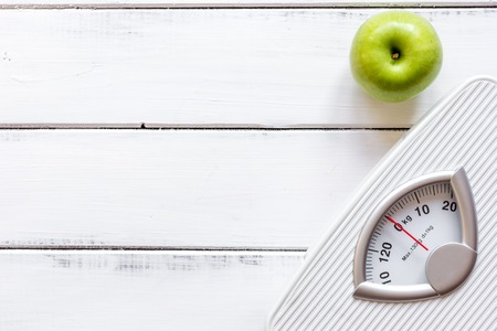 dietetics: floor scale and apple on wooden background top view. Stock Photo