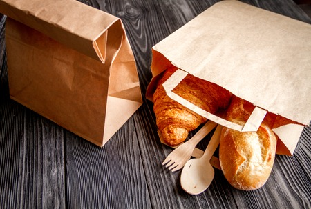 cup of coffee and croissant in paper bag on wooden background