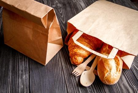 tasse de café et un croissant dans le sac de papier sur fond de bois