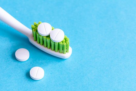 concept toothache with toothbrush and pills at blue background close up