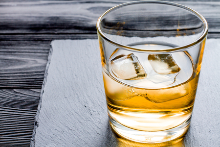 manlike: glass of whiskey on dark wooden background close up