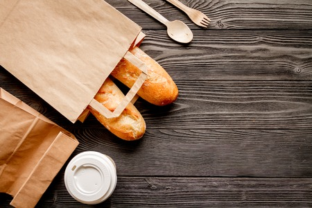 cup of coffee and bread in paper bag on wooden background top view