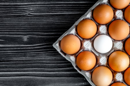 financial diversification: concept of correct choice eggs on dark wooden background top view Stock Photo