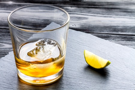 manlike: rum with ice in glass on dark background and lime close up