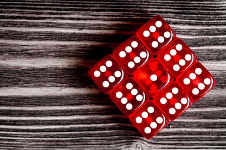 risk concept - playing dice at dark wooden background top view