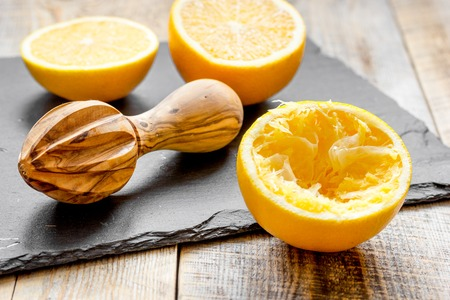 cut oranges in half and juicer on wooden background wooden background close up Stock Photo