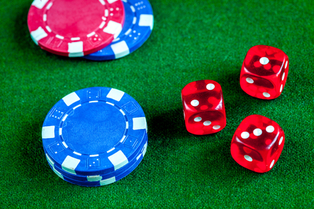 poker chips and dice on green background top view.