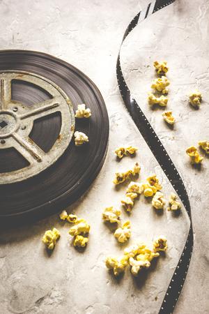 cinta pelicula: viendo la película con palomitas de maíz en el fondo gris de cerca.