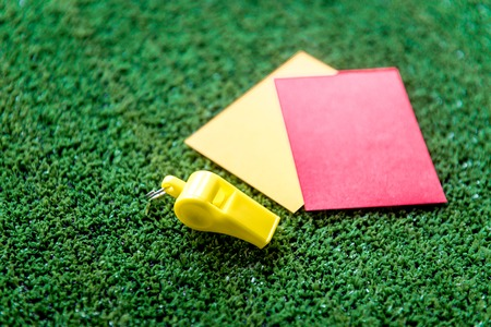 reprimand: red and yellow cards on green background close up mock up