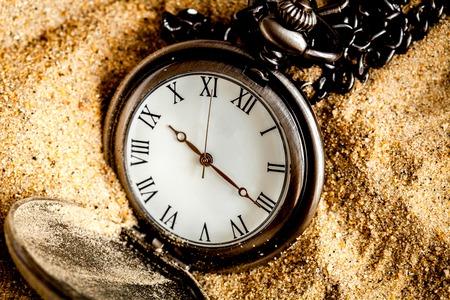 deadline concept pocket watch in sand background close up.