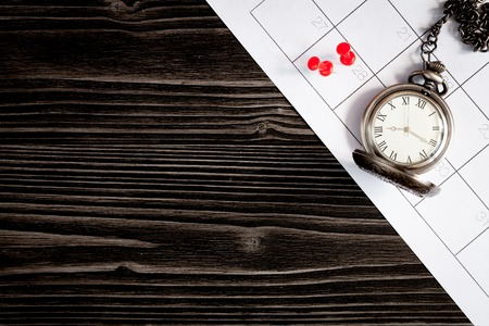 background calendar: deadline concept pocket watch on calendar background top view. Stock Photo