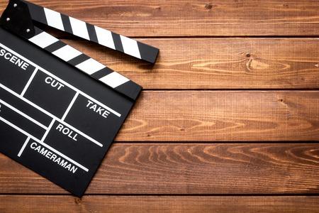 screenwriter: Screenwriter desktop with movie clapper board on wooden background top view