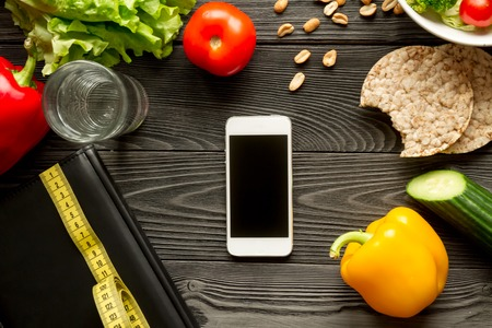 concept diet and smartphone with vegetables mock up on wooden background