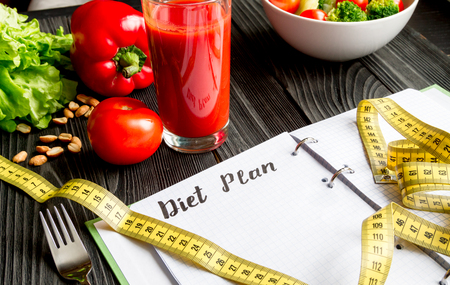 concept diet and slimming plan with vegetables close up mock up on wooden background