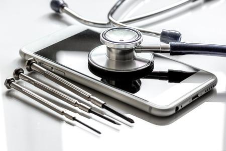 concept reparatie digitale gadgets met schroevendraaier op witte achtergrond close-up