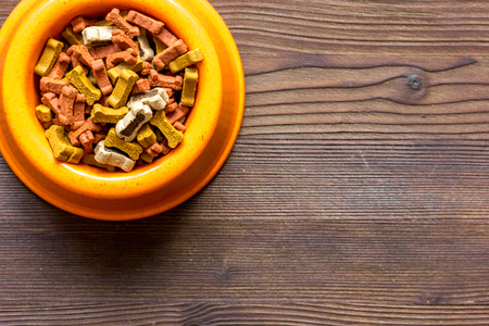 dry dog food in bowl on wooden background top view. Stock Photo