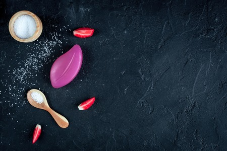 holistic view: organic cosmetics with extracts of berries on dark background top view