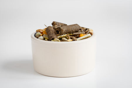 rodents: dry food for rodents in bowl on white background close up Stock Photo