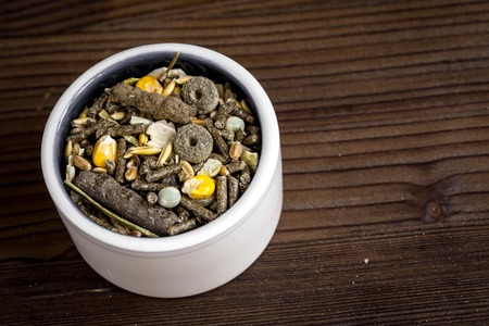 rodents: dry food for rodents in bowl on dark wooden background