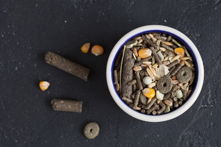 rodents: dry food for rodents in bowl on dark background top view.