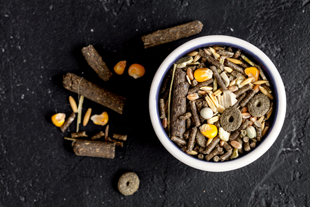 rodents: dry food for rodents in bowl dark background top view