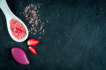 holistic view: organic cosmetics with extracts of berries dark background top view