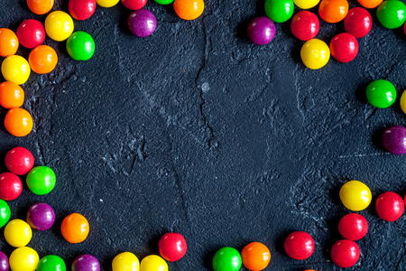 sweets and sugar candies on dark background top view. Imagens - 68986621