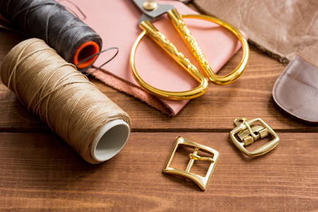 leather craft instruments on wooden background top view. Stock Photo