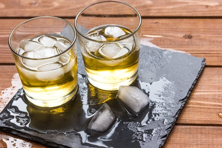 manlike: glass of whiskey on wooden background close up