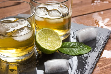 glass of whiskey on wooden background close up