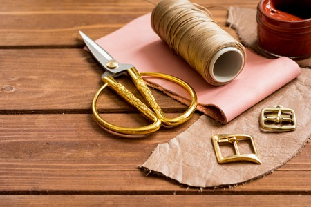 leather craft instruments on wooden background close up. Stock Photo