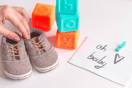 babys bootees and gift box on wooden background.