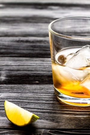 rum with ice in glass on dark wooden background and lime close up