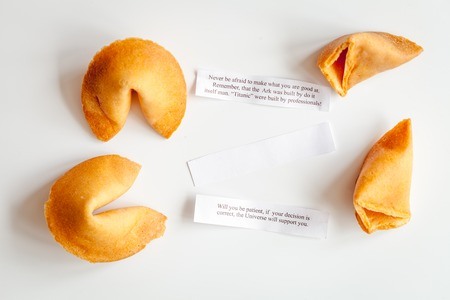 Chinese fortune cookie with prediction on white background close up top view