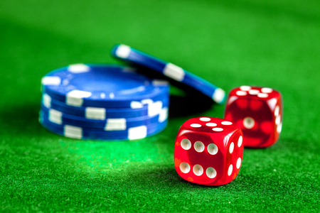 stack of chips to play poker on green background close up