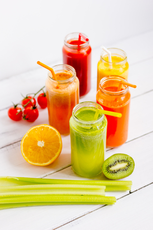 Fresh detox juices in glass bottles on white background. Stock Photo