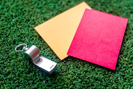 red and yellow cards on green background close up