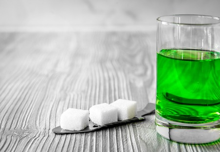 ajenjo: absinthe with sugar cubes and spoon on wooden background Foto de archivo
