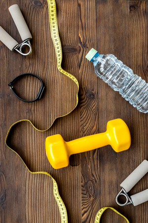 concept preparing to fitness sports equipment top view on wooden background. Stock Photo