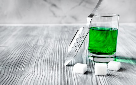 ajenjo: absinthe with sugar cubes and spoon on wooden background close up.