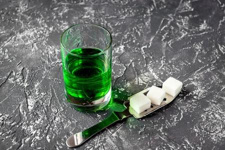 ajenjo: absinthe in glass on gray background close up. Foto de archivo