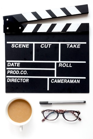 Screenwriter desktop with movie clapper board on white background top view Stock Photo