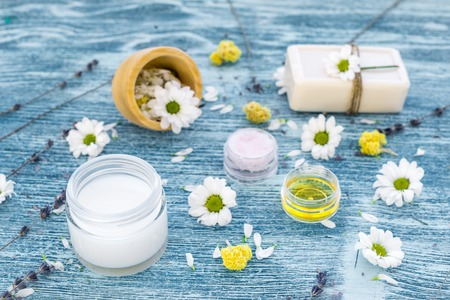 organic cosmetics with camomile on blue background