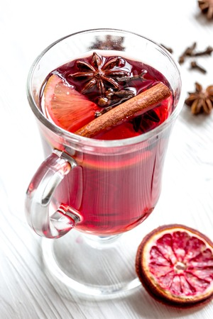 mulled wine with spices in cup on wooden background Stock Photo