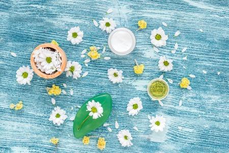 cremas faciales: organic cosmetics with camomile on blue background top view Foto de archivo