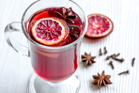 mulled wine with spices in cup on wooden background.