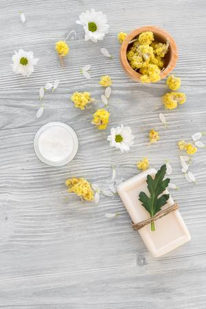 cremas faciales: organic cosmetics with camomile on wooden background top view Foto de archivo
