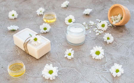 cremas faciales: organic cosmetics with camomile on stone background