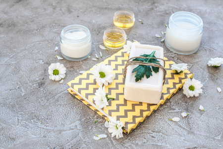 cremas faciales: organic cosmetics with camomile on stone background.