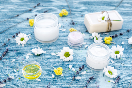 cremas faciales: organic cosmetics with camomile on blue background